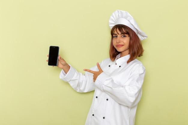 녹색 표면에 그녀의 스마트 폰을 들고 흰색 요리사 정장에 전면보기 여성 요리사