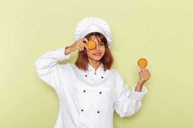小さなクッキーを保持し、緑の表面に笑みを浮かべて白いクックスーツで正面図の女性料理人