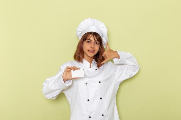 緑の表面にポーズをとって白いカードを保持している白いクックスーツの正面図女性料理人