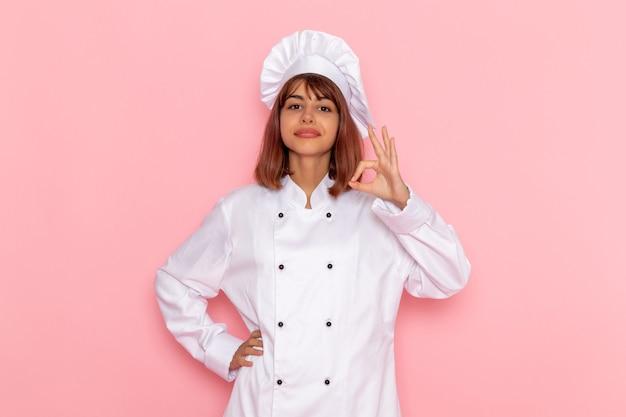ピンクの表面に笑みを浮かべて白いクックスーツの正面の女性料理人