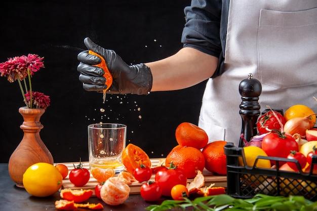 Front view female cook making tangerine juice on the black salad health meal food job diet vegetable fresh drink fruit