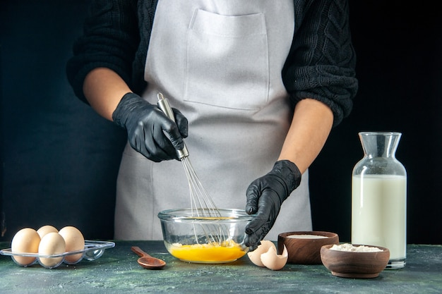 Front view female cook mixing eggs for dough on dark pastry cake pie worker hotcake dough cuisine job