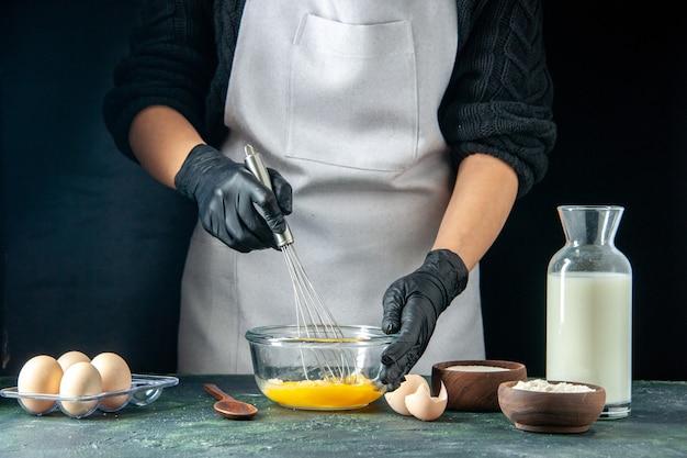 전면 보기 여성 요리사는 어두운 페이스트리 케이크 파이 작업자 핫케이크 반죽 요리 작업에 반죽을 위해 계란을 섞습니다.