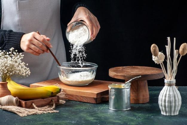 Cuoca di vista frontale che versa la noce di cocco nel piatto con latte condensato su fondo scuro