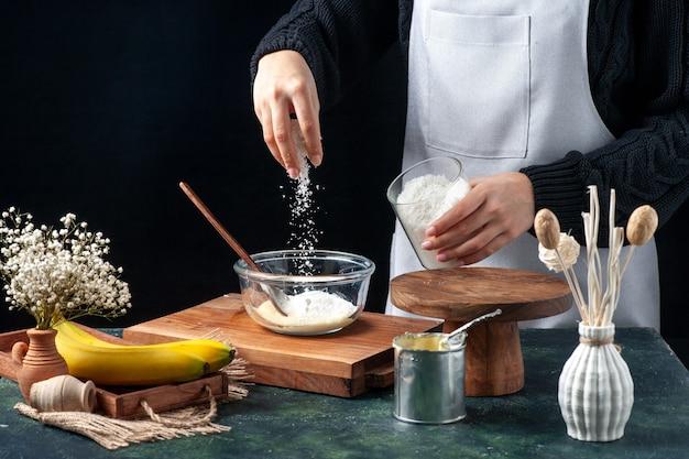 暗い背景に練乳でプレートにココナッツを注ぐ正面図の女性料理人