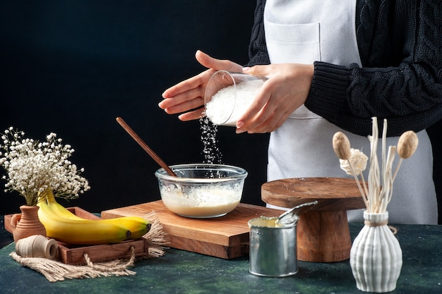 Front view female cook pouring coconut powder onto condensed milk on a dark background