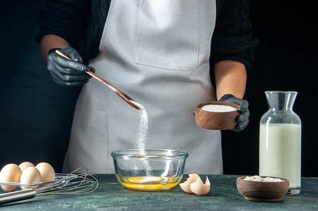 Front view female cook pouring flour into the eggs for dough on dark pastry cake pie bakery worker cuisine job