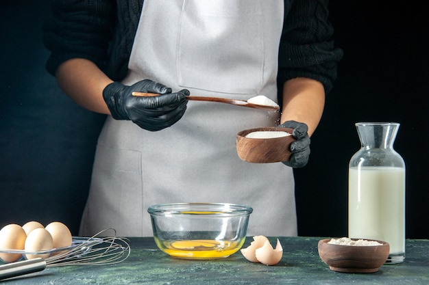 Front view female cook pouring flour into the eggs for dough on a dark pastry cake pie bakery worker hotcake cuisine job