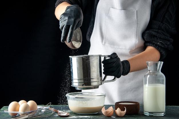 전면 보기 여성 요리사는 어두운 핫케이크 페이스트리 케이크 파이 요리 작업 반죽 작업자에 계란에 밀가루를 붓는다
