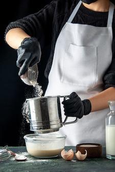 Вид спереди женщина-повар наливает муку в яйца на темном горячем пироге, пироге, пироге, кухне