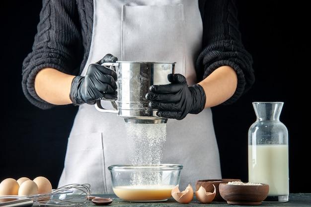 Вид спереди женщина-повар засыпает муку в тарелку с яйцами для теста на темном тесте, пирог, пирог, кухня, работа, тесто для горячего