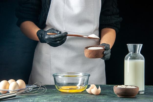 전면 보기 여성 요리사는 어두운 페이스트리 케이크 파이 빵집 작업자 핫케이크 요리 작업에 반죽을 위해 계란에 밀가루를 붓는다