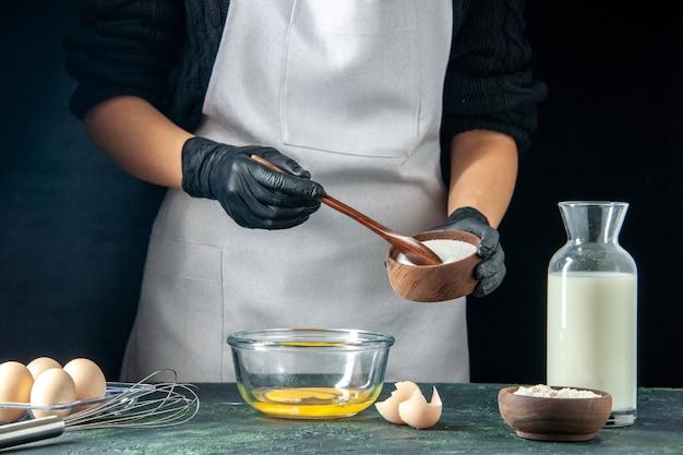 Вид спереди повар-женщина, сыпающая муку в яйца для теста на темном тесте, пирог, пирог, работник пекарни, хоткейк, кухня, работа