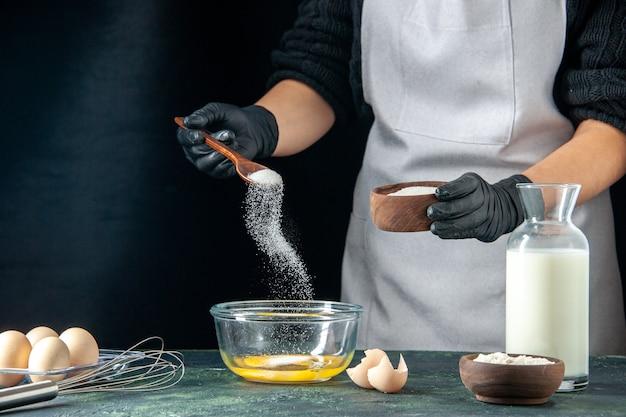 전면 보기 여성 요리사는 어두운 페이스트리 케이크 파이 작업자 핫케이크 반죽 요리 작업 빵집에 반죽을 위해 계란에 밀가루를 붓는다