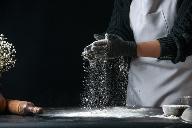 Front view female cook pouring flour on table for dough on dark dough egg cuisine job bakery hotcakes pastry kitchen