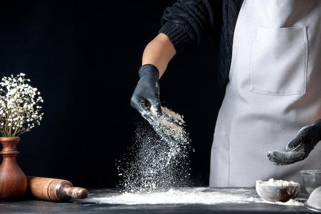 Vista frontale cuoca versando la farina sul tavolo per l'impasto su un impasto scuro uovo lavoro panetteria hotcake pasticceria cucina cucina