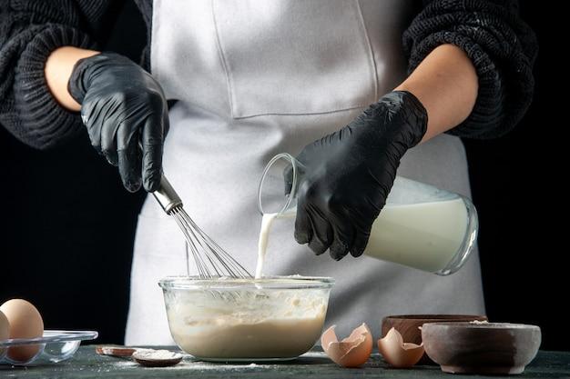 ダークホットケーキペストリーケーキパイ料理の仕事の労働者の生地のために卵と砂糖にミルクを注ぐ正面図の女性料理人