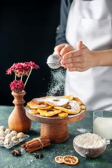 Cuoca vista frontale che versa zucchero in polvere su anelli di ananas essiccati su frutta scura che cucina lavoro torta pasticceria da forno