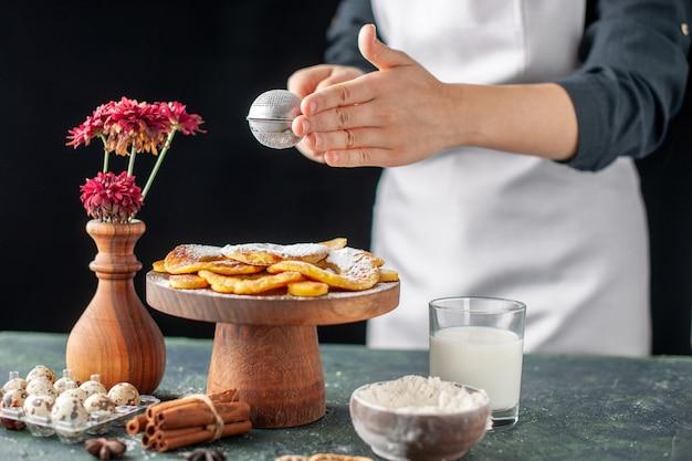 Vista frontale cuoca versando zucchero in polvere su anelli di ananas essiccati su un lavoro di frutta scura torta di pasticceria torta di cottura da forno