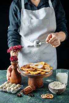 正面図女性料理人がダークフルーツ料理の仕事の労働者の乾燥パイナップルリングに砂糖粉を注ぐペストリーケーキパイベーカリー