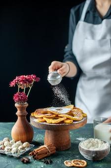 Вид спереди женщина-повар наливает сахарную пудру на сушеные кольца ананаса на темные фрукты, готовит кондитерские изделия, пирог, пирог
