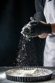 Cuoca di vista frontale che versa farina bianca nella padella sulla torta di uova scure panetteria cucina torta hotcake cucina pasta