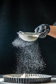 Cuoca di vista frontale che versa farina bianca nella padella su una torta di uova scure da forno pasticceria cucina cucina torta di pasta hotcake