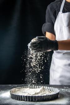Вид спереди женщина-повар наливает белую муку в сковороду на темный яичный пирог, выпечка, кондитерская, кухня, тесто, пирог, горячий пирог, кухня