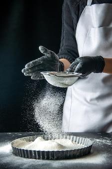 Вид спереди женщина-повар наливает белую муку в сковороду на темный яичный торт, выпечка, кондитерская, кухня, тесто, горячее