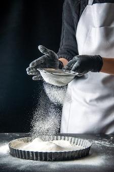 Вид спереди женщина-повар наливает белую муку в сковороду на темный яичный торт, выпечка, выпечка, кухня, пирог, горячий пирог