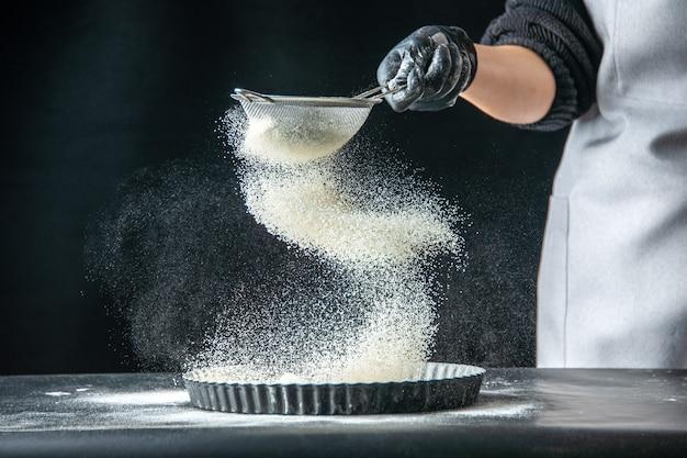 正面図女性料理人が暗い卵の仕事ベーカリーペストリーキッチン料理生地の鍋に白い小麦粉を注ぐ