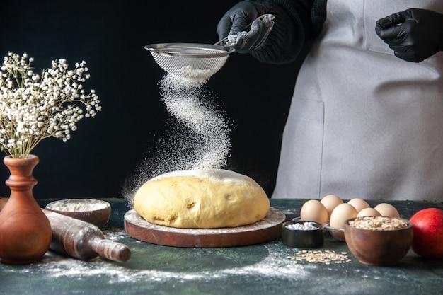 正面図女性料理人が暗いペストリーの仕事で生の生地に白い小麦粉を注ぐ生の生地ホットケーキベーカリーパイオーブン