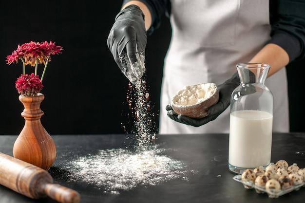 Вид спереди женщина-повар наливает белую муку на стол для теста на темные фрукты, выпечка, выпечка, выпечка
