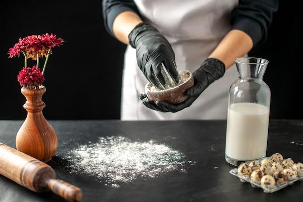 Cuoca vista frontale che versa farina bianca sul tavolo per l'impasto su frutta scura lavoro pasticceria torta torta cottura da forno