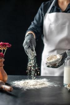 Cuoca vista frontale che versa farina bianca sul tavolo per l'impasto su un lavoro scuro torta di pasticceria panetteria cottura pasta cuocere la torta