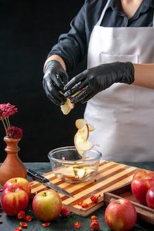 Вид спереди женщина-повар кладет яблоки в тарелку на темных фруктовых соках, диетические пироги, цветной салат, еда, еда, экзотический рабочий торт