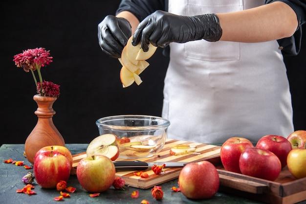 Cuoco femminile di vista frontale che mette le mele affettate nel piatto sul lavoro esotico del succo di dieta del pasto della frutta scura