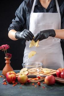 正面図女性料理人は、スライスしたリンゴをダークフルーツダイエットサラダフードミールエキゾチックジュースワークのプレートに入れます