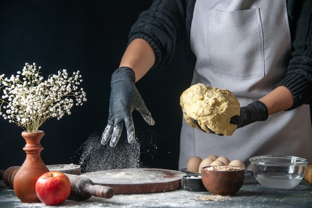 Vista frontale cuoca stendere la pasta sul lavoro scuro torta di pasta forno pasticceria cucina hotcake cucina panetteria uova