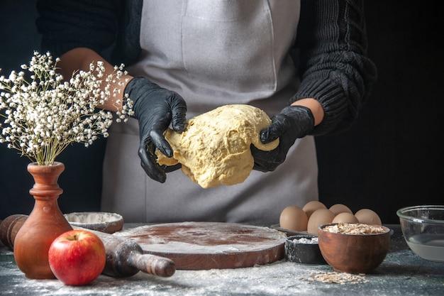 Вид спереди женщина-повар раскатывает тесто на темной работе, сырое тесто, пирог, духовка, хоткейк, выпечка, яйцо