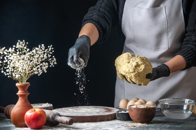 Вид спереди женщина-повар раскатывает тесто на темной работе, тесто, пирог, печь, выпечка, кухня, хоткейк, кухня, выпечка, яйцо.