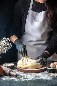 Женщина-повар, раскатывающая тесто на темной выпечке, сырое тесто, горячая выпечка, печь для пирогов, вид спереди