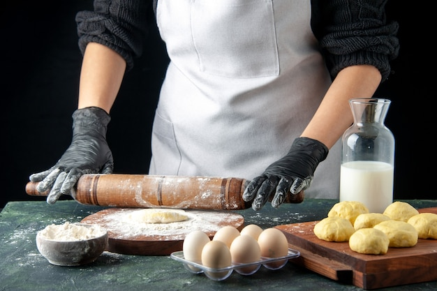 Front view female cook rolling out dough with flour on dark cake job oven hotcake dough bake pie worker eggs cuisine