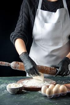 Vista frontale cuoca stendere l'impasto con la farina su una torta scura lavoro forno torta hotcake lavoratore uovo cucina pasta