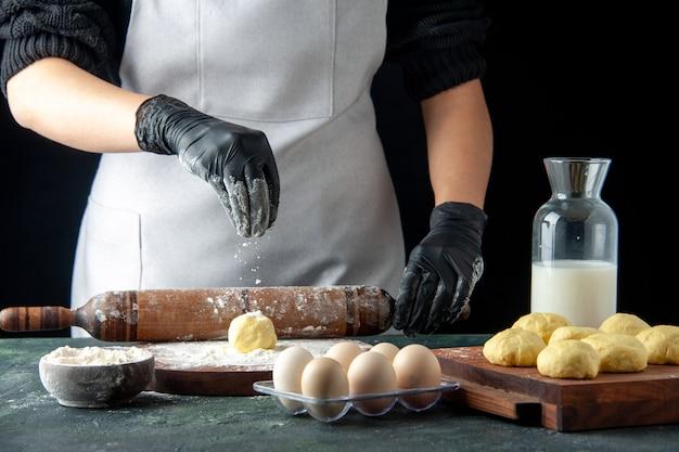 Vista frontale cuoca stendere l'impasto con la farina sul lavoro scuro cucina forno impasto hotcake cuocere torta torta lavoratore uovo
