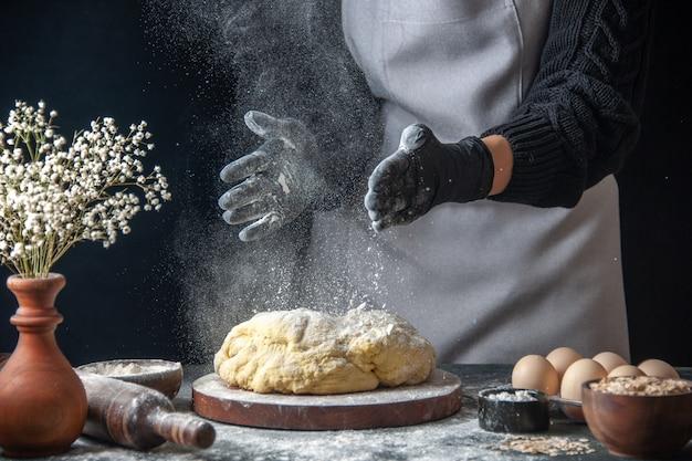Cuoca vista frontale che stende la pasta con la farina sul lavoro scuro pasta cruda panetteria torta forno pasticceria hotcake