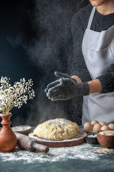Front view female cook rolling out dough with flour on a dark job raw dough pie oven pastry hotcake bakery