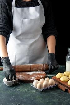 전면 보기 여성 요리사 어두운 작업 요리에 밀가루와 반죽을 롤링 핫케이크 생 반죽 베이킹 케이크 파이 작업자