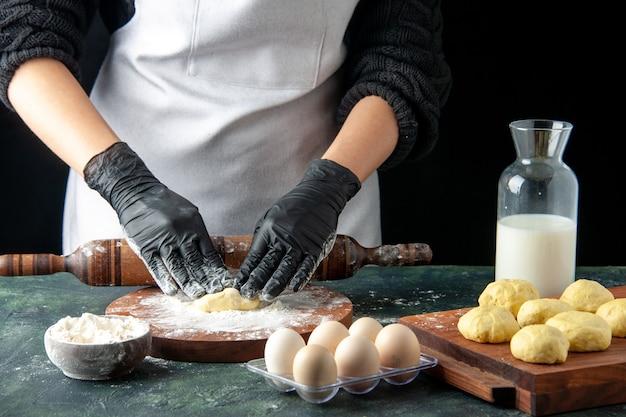 暗い仕事の料理オーブンのホットケーキで小麦粉と生地を展開する正面図の女性料理人