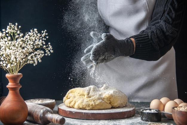 正面図女性料理人が暗い仕事で小麦粉で生地を広げている生の生地ベーカリーパイオーブンペストリーホットケーキ